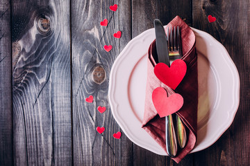 Valentine day table setting. Pink plate, knife and fork on wooden background table. Top view and copy space. Love concept.