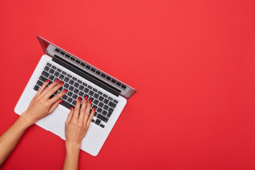 Woman skinny hands working on a silver laptop on a red desktop a