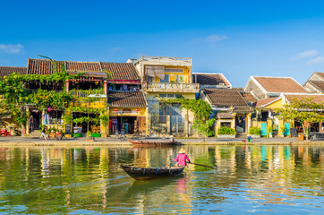 Woman crossing a river on a boat in Hoi An during mid day