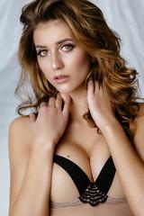 beautiful sexy brunette girl in lingerie posing against white bricks. Advertising Space