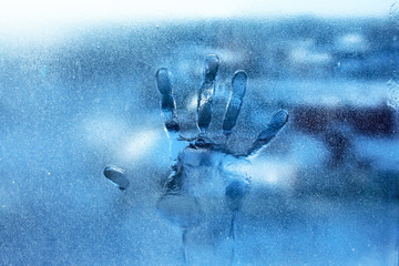 The imprint of the palm of human hand on frozen window glass in cool colors. Conceptual photography with an idea for reflection