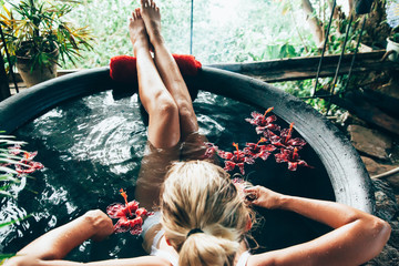 Woman relaxing in outdoor spa bath