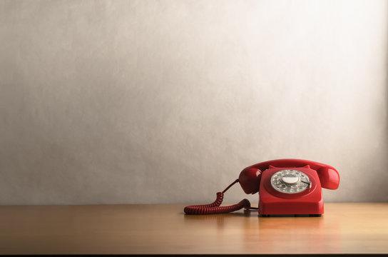 Retro Red Telephone on Light Wood Veneer Desk