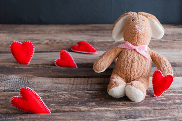 Fluffy toy bunny with felt hearts.  Postcard to Valentine's Day.