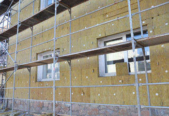 External wall insulation. Solid wall insulation. Energy efficiency house wall renovation for energy saving. Exterior house wall heat insulation with mineral wool, building  under construction.