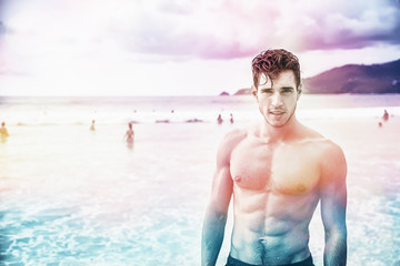 Heavily filtered shot of a handsome young man standing on a beach in Phuket Island, Thailand, shirtless wearing boxer shorts, showing muscular fit body