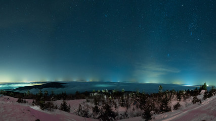 winter night sky above mountains with stars and city lights in the distance