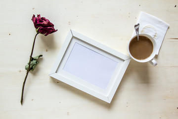 dry rose and picture frame with coffee