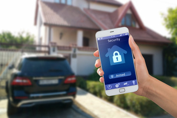 Smartphone with home security app in a hand on the building background