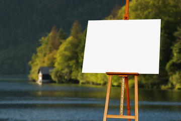 Blank painter artist canvas on easel with lake in background
