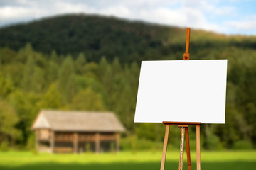 Blank painter artist canvas on easel with mountain in background