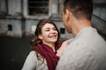Smiling girl with braces. Young couple wearing on tied warm swea