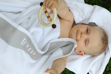 ein Baby liegt , in weisses Tuch gewickelt, auf dem rücken, und versucht ein Spielzeug zu greifen