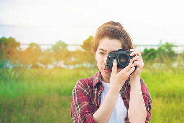 young woman photographer taking at park
