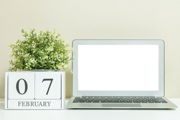 White wooden calendar with black 7 february word with white blank space at center of computer notebook on white wood desk and cream wallpaper textured background in selective focus at the calendar