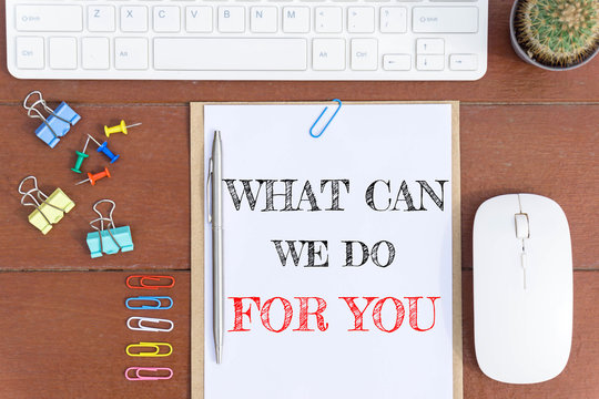 Text What can we do for you on white paper which has keyboard mouse pen and office equipment on wood background / business concept.
