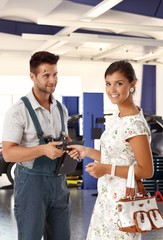 Happy attractive young woman at auto repair shop