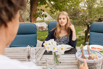 Teenage girl talking to mother at table in yard