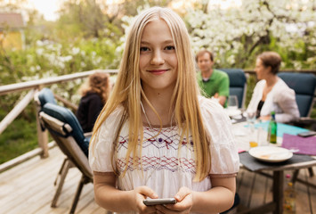 Portrait of teenage girl holding smart phone at yard with family sitting in background