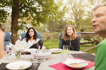 Teenage girls sitting with father at table in yard
