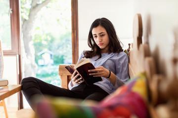 Teenage girl reading book while sitting on sofa