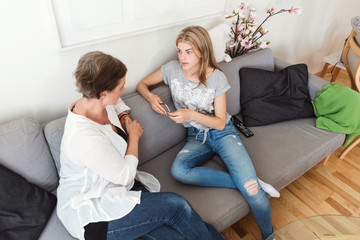 Mother and daughter talking while sitting on sofa at home