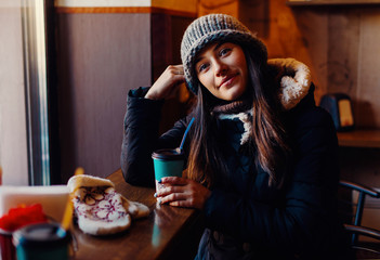 Young beautiful happy smiling girl holding takeaway cup with hot liquid, drinking coffee or tea. Model wearing stylish knitted winter clothes, accessories. Indoor. Close up.