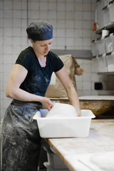 Baker working with dough at kitchen counter in bakery