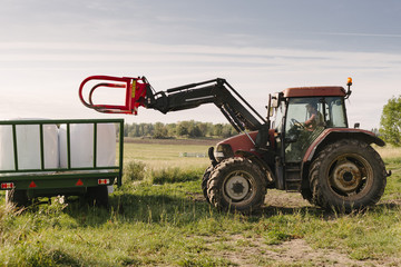 Farmer riding tractor keeping silage bales in cart at farm