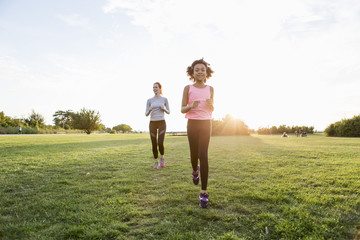 Girl and woman jogging on grass at park against sky during sunset