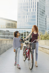 Mother and daughter walking with bicycle on footbridge in city