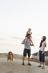 Mother looking at girl enjoying sitting on shoulder of father standing against sky