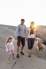 Family walking with dog on rock formation against clear sky