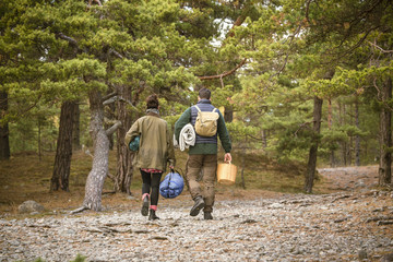 Rear view of couple carrying sleeping bags and basket in forest