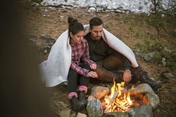 Couple wrapped in blanket while sitting by fire pit at campsite