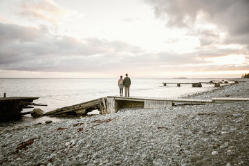 Rear view of couple standing on jetty at beach against sky during sunset