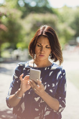 Mature businesswoman using smart phone on footpath in park during summer
