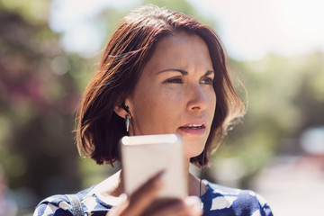 Thoughtful businesswoman looking away while holding smart phone in park during summer