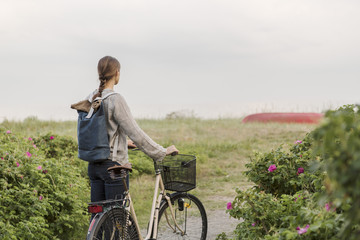 Rear view of woman walking with bicycle on footpath amidst plants against clear sky