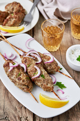 Barbecued kofta -traditional shish kebab from lamb meat with white sauce and wine.