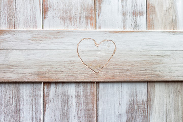 Heart shaped carving on a wooden fence