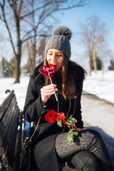 Beautiful young girl sitting on bench at park and holding a lollipop in heart shape and red rose.