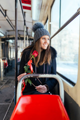 Beautiful young woman sitting in tram, holding red rose and looking through window.