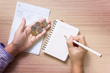 Coins on hand with bank book account background, hand writing