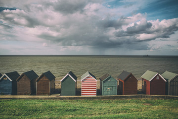 Row of beach huts of cloudy day with rain clouds in Kent, England