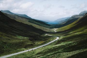 Empty road passing through grassy landscape