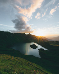 Scenic view of landscape with lake and mountains during sunrise