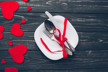 Valentine's Day. red felt heart ,cutlery,fork,knife,plate and decor on wooden background