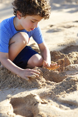 Young boy playing in sand at the beach