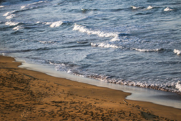 Sea with small foam wave and beach.